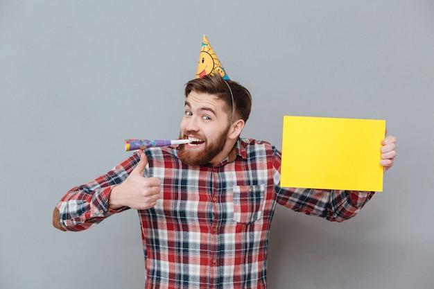 Giovane uomo barbuto allegro di compleanno che tiene bordo in bianco