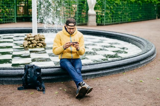 Giovane uomo barbuto attraente in abbigliamento casual che si siede vicino alla fontana di pietra che è concentrata nello schermo del suo smartphone