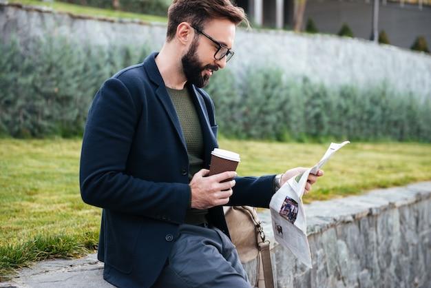 Giovane uomo barbuto bello che si siede all'aperto leggendo giornale