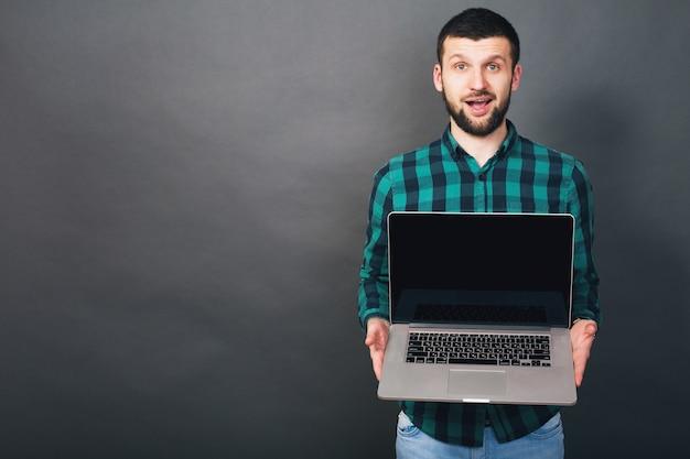 Giovane uomo barbuto bello hipster che tiene il computer portatile in mano, camicia a scacchi verde, emozione positiva, felice, sorridente, sorpresa, sfondo grigio