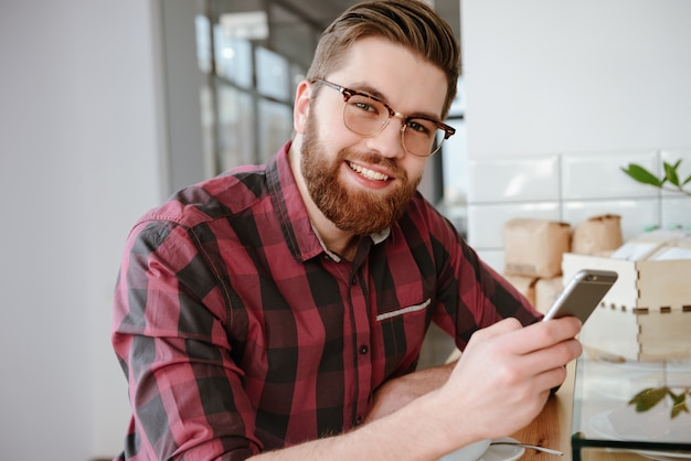 Giovane uomo barbuto che controlla il suo newsfeed sui social media