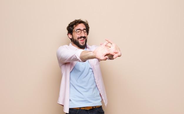 Giovane uomo barbuto che esprime un concetto sulla parete piana