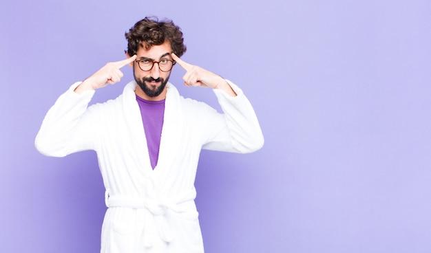 Giovane uomo barbuto che indossa un accappatoio con uno sguardo serio e concentrato, di brainstorming e pensando a un problema stimolante