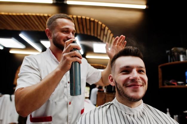 Giovane uomo barbuto che ottiene taglio di capelli dal parrucchiere mentre sedendosi nella sedia al parrucchiere. anima da barbiere.