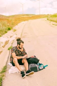 Giovane uomo barbuto che per mezzo del computer portatile che si siede sulla strada