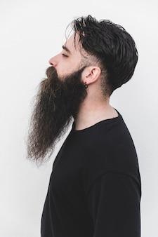 Giovane uomo barbuto che si leva in piedi contro la priorità bassa bianca
