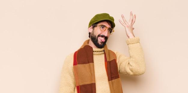 Giovane uomo barbuto che solleva il palmo sulla fronte pensando oops, dopo aver fatto uno stupido errore o aver ricordato, sentendosi stupido