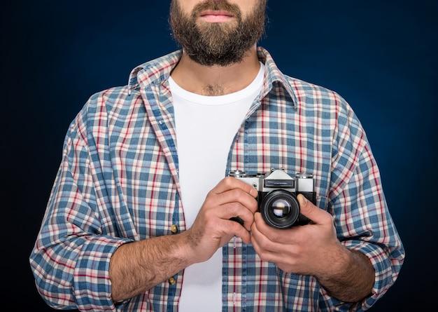 Giovane uomo barbuto che tiene macchina fotografica vecchio stile.