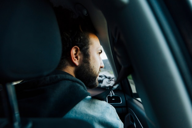 Giovane uomo barbuto che viaggia in auto