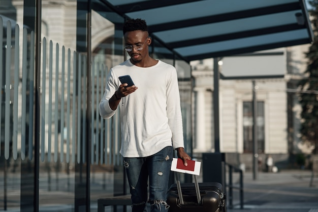 Giovane uomo barbuto con bagagli e telefono
