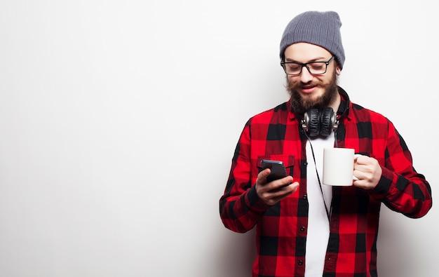 Giovane uomo barbuto con il cellulare