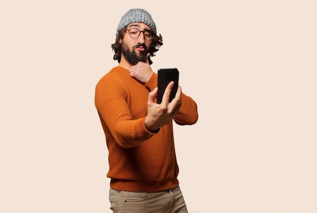 Giovane uomo barbuto con uno smart phone