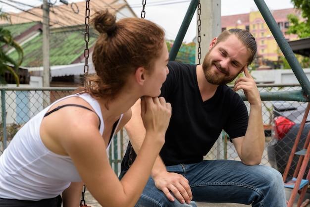 Giovane uomo barbuto felice che esamina giovane bella donna che sorride nelle vie all'aperto