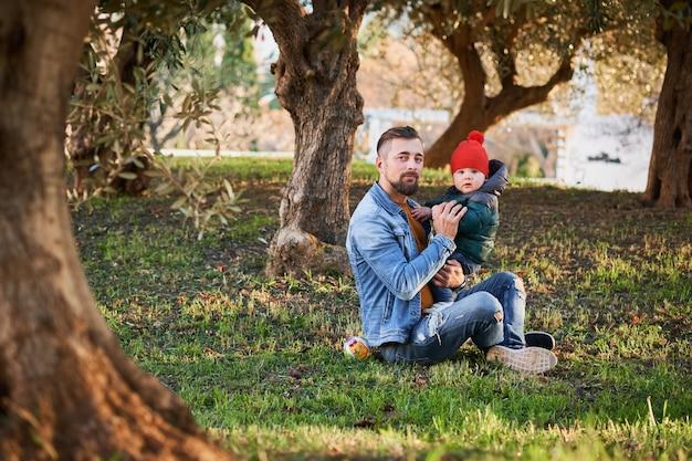 Giovane uomo barbuto felice che gioca con il suo piccolo figlio nel parco