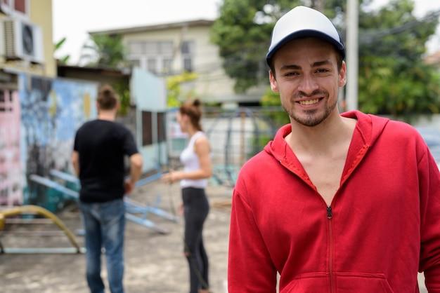 Giovane uomo barbuto felice che sorride mentre indossando cappuccio nelle vie all'aperto