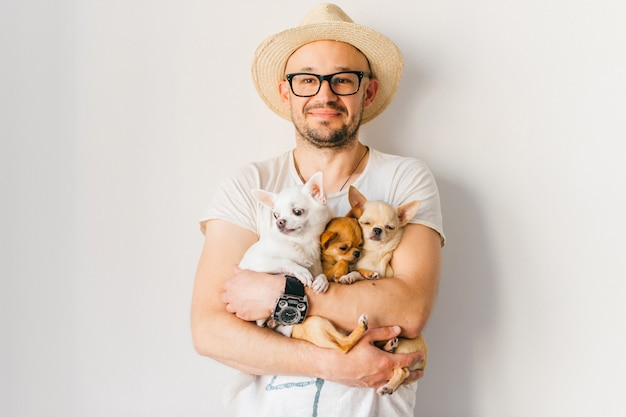 Giovane uomo barbuto felice dei pantaloni a vita bassa in cappello di paglia e vetri che tengono in mano tre cuccioli della chihuahua