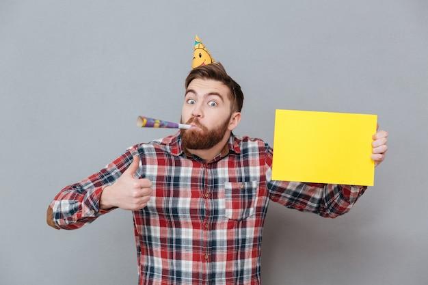 Giovane uomo barbuto felice di compleanno che tiene bordo in bianco