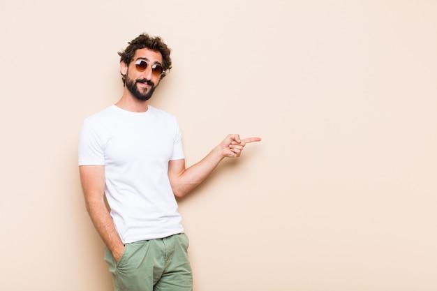 Giovane uomo barbuto freddo che mostra o indica