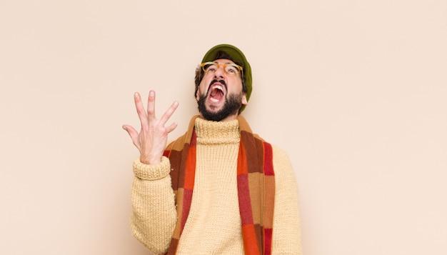 Giovane uomo barbuto freddo che sembra arrabbiato, infastidito e frustrato che grida wtf o cosa c'è di sbagliato in te