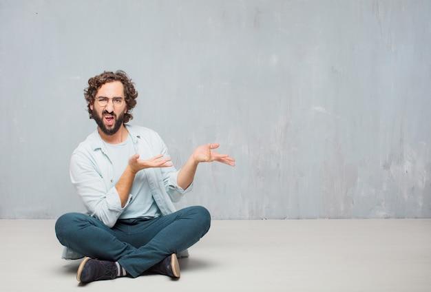 Giovane uomo barbuto freddo che si siede sul pavimento. fondo della parete del grunge