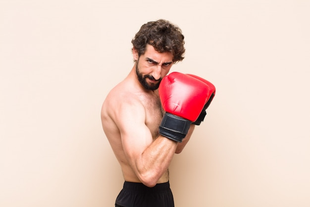 Giovane uomo barbuto freddo con guantoni da boxe e concetto di fitness di combattimento