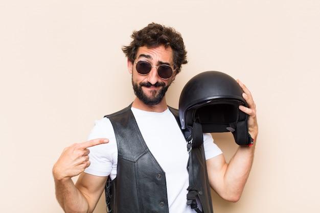 Giovane uomo barbuto freddo con un casco che punta a destra