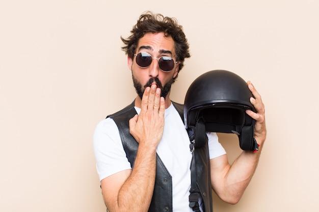 Giovane uomo barbuto freddo con un casco e un'espressione spaventata