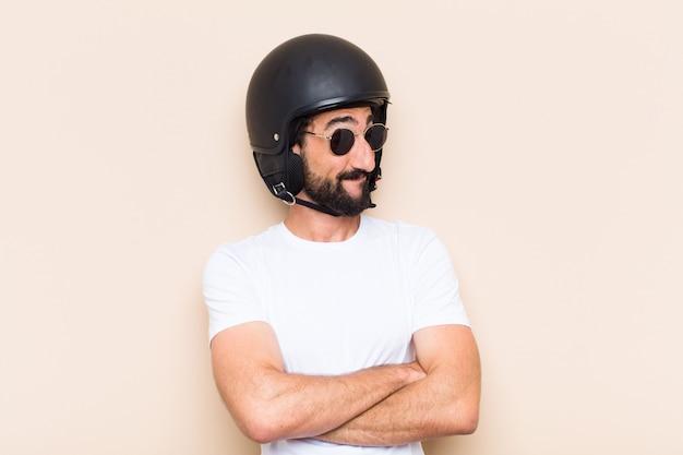 Giovane uomo barbuto freddo con un casco soddisfatto e felice