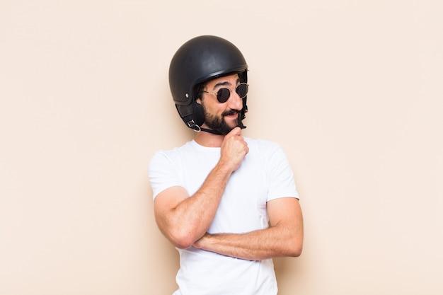 Giovane uomo barbuto freddo con un pensiero del casco
