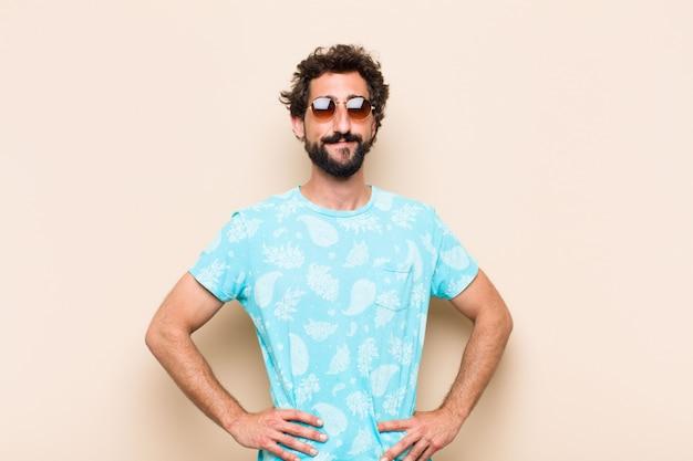 Giovane uomo barbuto freddo felice e soddisfatto. concetto di vacanze