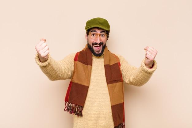 Giovane uomo barbuto freddo felice, positivo e di successo, che celebra la vittoria, i successi o la buona fortuna
