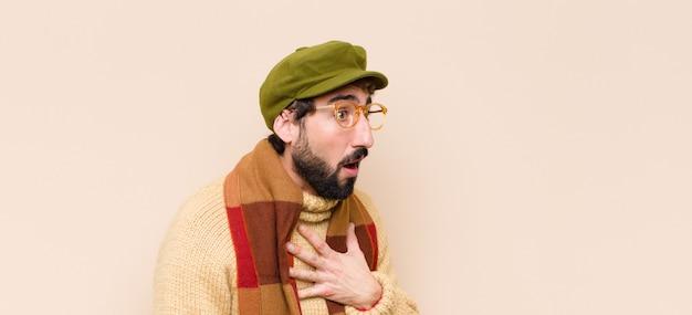 Giovane uomo barbuto freddo sentirsi scioccato e sorpreso, sorridendo, prendendosi per mano, mostrando gratitudine