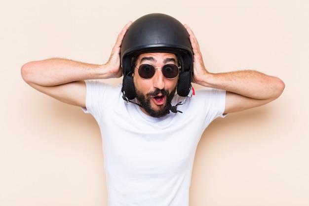 Giovane uomo barbuto freddo sorpreso con un casco