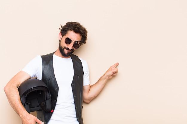 Giovane uomo barbuto fresco con un casco rivolto di lato