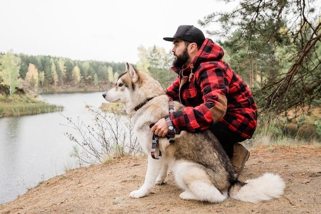 Giovane uomo barbuto in abbigliamento casual che abbraccia il cane husky mentre trascorre del tempo in riva al lago in ambiente rurale