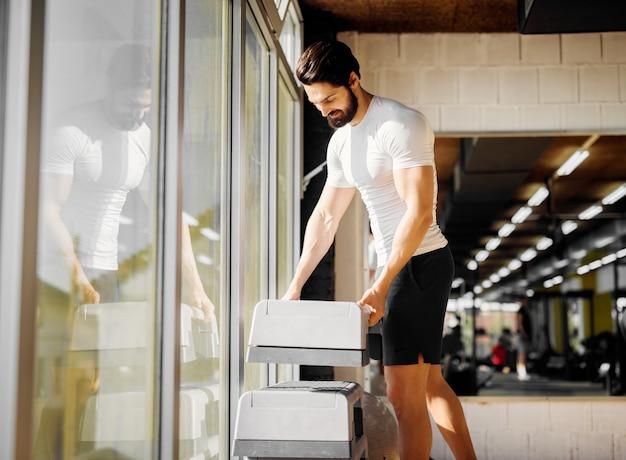 Giovane uomo barbuto muscoloso bello prendendo stepper dalla fila vicino alla finestra in palestra.