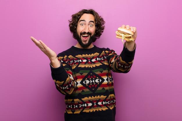 Giovane uomo barbuto pazzo che mangia un hamburger