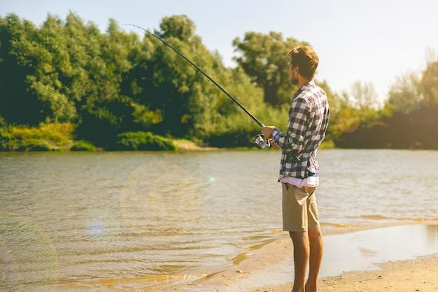 Giovane uomo barbuto pesca in piedi sulla riva del fiume sabbiosa con canna da pesca durante l'estate.