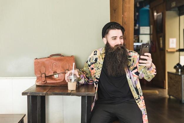 Giovane uomo barbuto seduto nella caffetteria prendendo selfie sul cellulare