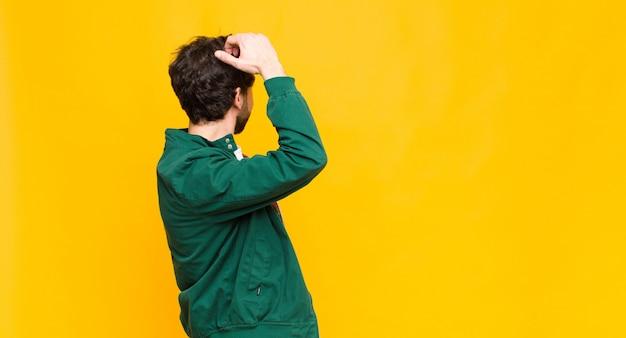 Giovane uomo barbuto sentirsi confuso e confuso, pensando a una soluzione, con la mano sull'anca e l'altro sulla testa, vista posteriore contro la parete piatta