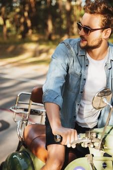 Giovane uomo barbuto serio bello che si siede sul motorino