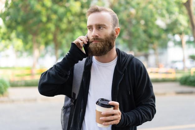 Giovane uomo barbuto serio che cammina in città e che invita telefono
