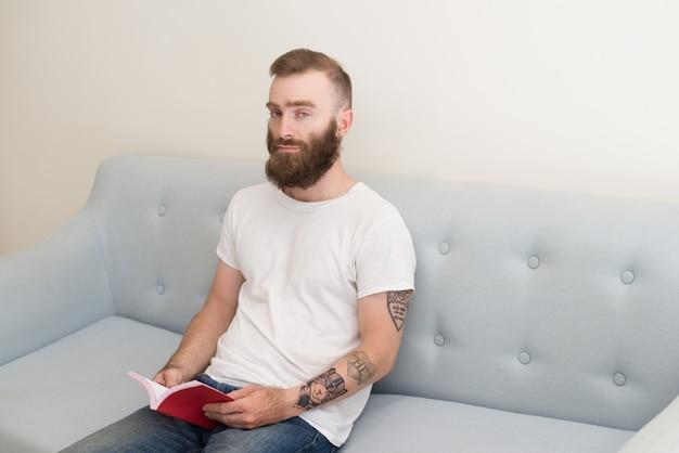 Giovane uomo barbuto serio che si siede sul sofà e sul libro di lettura