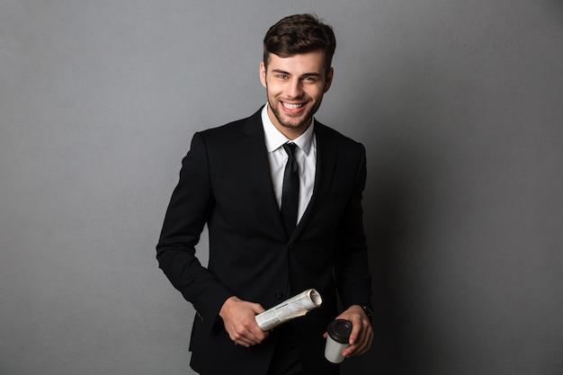 Giovane uomo barbuto sorridente in abbigliamento formale che tiene il giornale e la tazza di caffè,