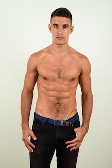 Giovane uomo bello a torso nudo su sfondo colorato
