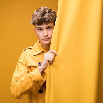 Giovane uomo bello accanto a una tenda in una scena gialla