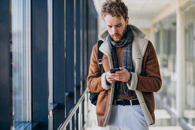 Giovane uomo bello all'aeroporto parlando al telefono