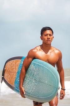 Giovane uomo bello bagnato tutto il corpo, tenendo in mano la tavola da surf camminando sulla spiaggia