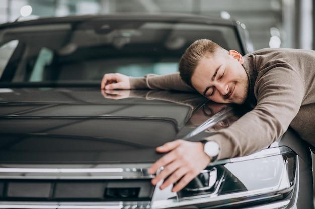 Giovane uomo bello che abbraccia un'automobile in una sala d'esposizione dell'automobile