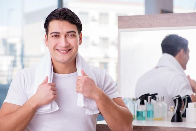 Giovane uomo bello che applica crema per il viso